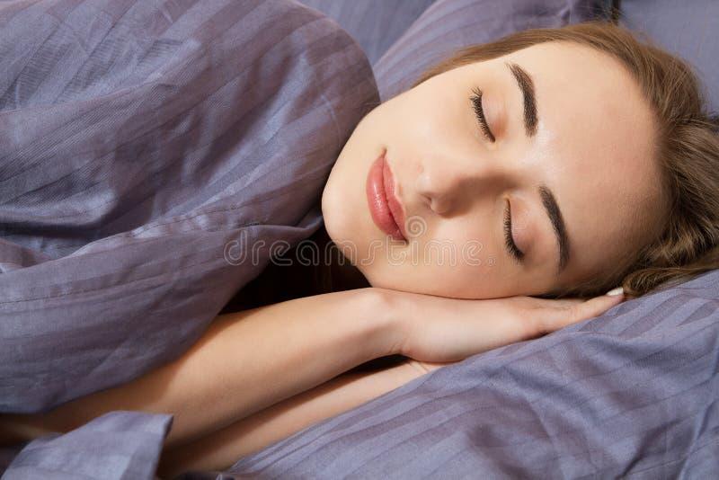 Bella giovane donna del ritratto che dorme mentre trovandosi nel suo letto Concetto della reintegrazione di resto e piacevole per immagine stock libera da diritti