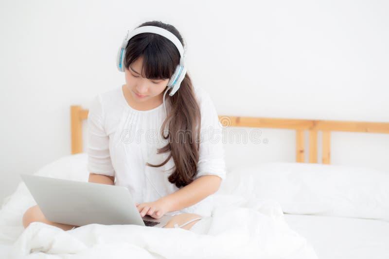 Bella giovane donna dell'Asia che si trova nella camera da letto facendo uso del computer portatile che mostra video chiacchierat immagini stock libere da diritti