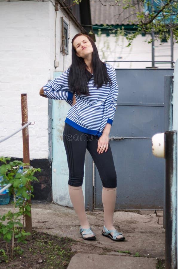 Bella giovane donna della brunetta in rivestimento a strisce piacevole, trou di sport immagine stock
