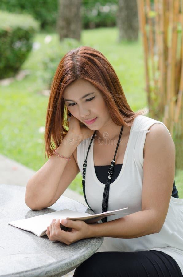 Bella giovane donna della testarossa che scrive un taccuino fotografie stock