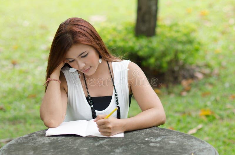 Bella giovane donna della testarossa che scrive un taccuino fotografia stock libera da diritti