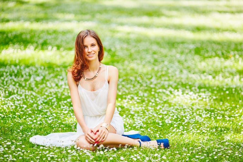 Bella giovane donna della testarossa sul prato con i fiori bianchi immagine stock