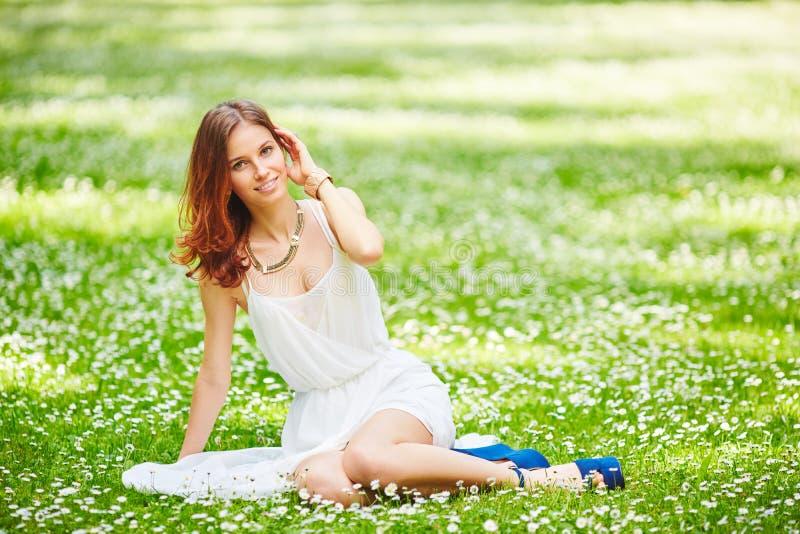 Bella giovane donna della testarossa sul prato con i fiori bianchi fotografia stock libera da diritti