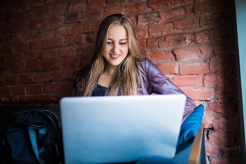 Bella giovane donna delle free lance che per mezzo del computer portatile che si siede alla tavola del caffè Ragazza sorridente f fotografie stock