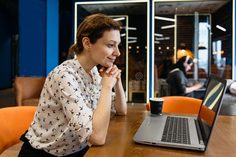 Bella giovane donna delle free lance che per mezzo del computer portatile che si siede alla tavola del caff? Lavoro sorridente fe fotografia stock libera da diritti
