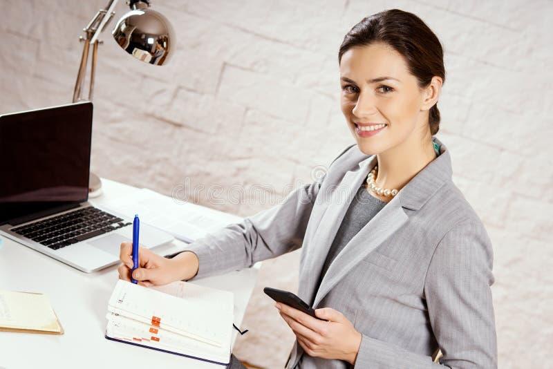 Bella giovane donna di affari che posa nell'ufficio con un telefono in sua mano immagini stock