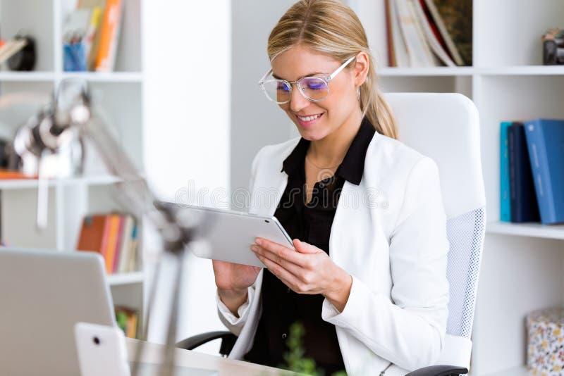 Bella giovane donna di affari che utilizza la sua compressa digitale nell'ufficio immagini stock