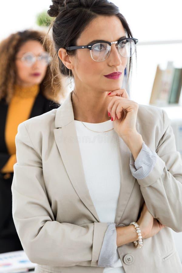 Bella giovane donna di affari due che posa nell'ufficio immagini stock