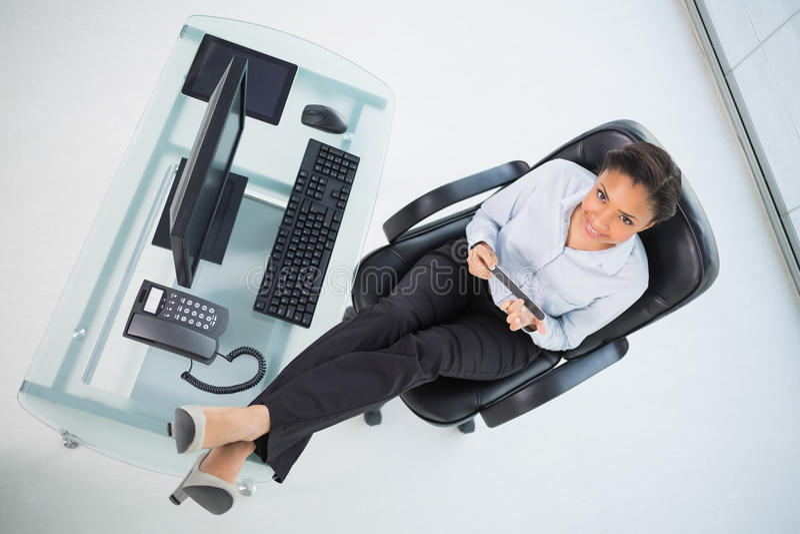 Bella giovane donna di affari mora che archiva i suoi chiodi che si siedono al suo scrittorio immagini stock