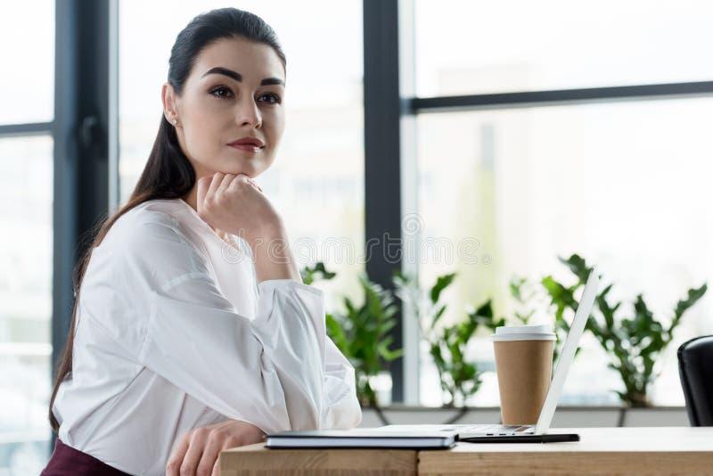 bella giovane donna di affari pensierosa che si siede alla tavola ed a distogliere lo sguardo fotografia stock