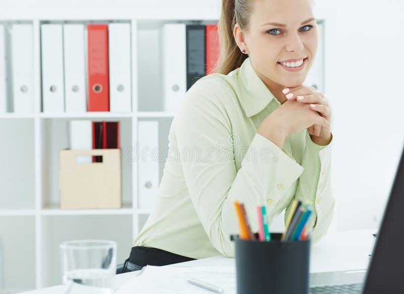 Bella giovane donna di affari sorridente che si siede alla tavola con il computer portatile in ufficio fotografia stock libera da diritti