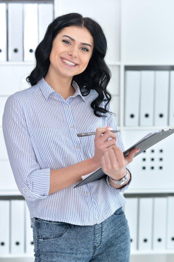 Bella giovane donna di affari in ufficio con la cartella immagine stock libera da diritti