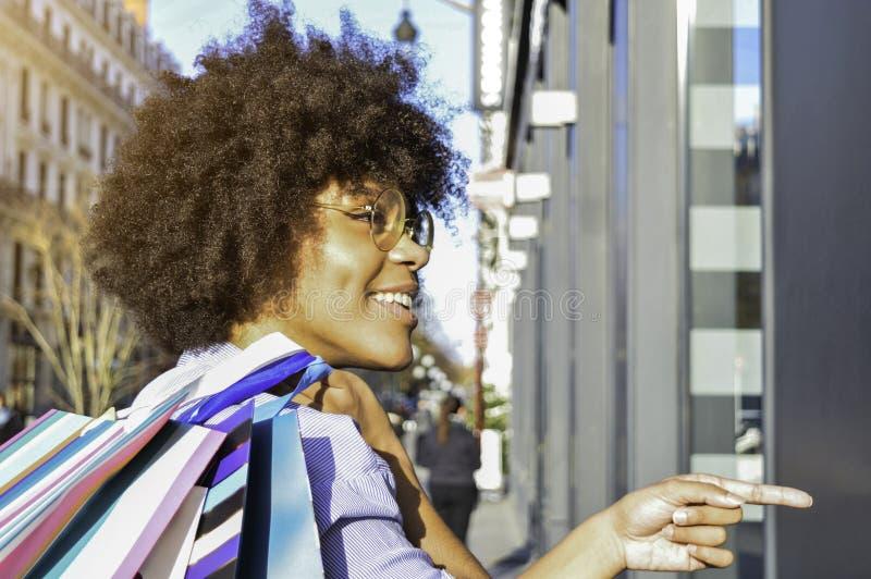 Bella giovane donna di colore sorridente che tiene i sacchetti della spesa sulla sua spalla e che indica ad un negozio Concetto c fotografia stock