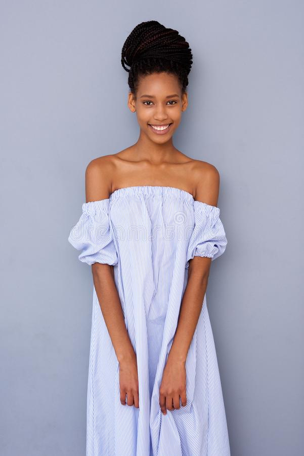 Bella giovane donna di colore in vestito che umilia fondo grigio immagini stock