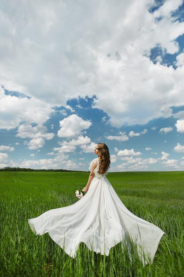 Bella giovane donna di modello con l'acconciatura di nozze in vestito lungo bianco che posa in un campo verde nel giorno soleggia fotografia stock libera da diritti