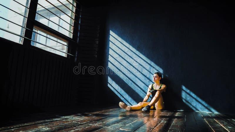 Bella giovane donna di pugilato che riposa dopo la formazione dopo la perforazione nella palestra fotografie stock libere da diritti