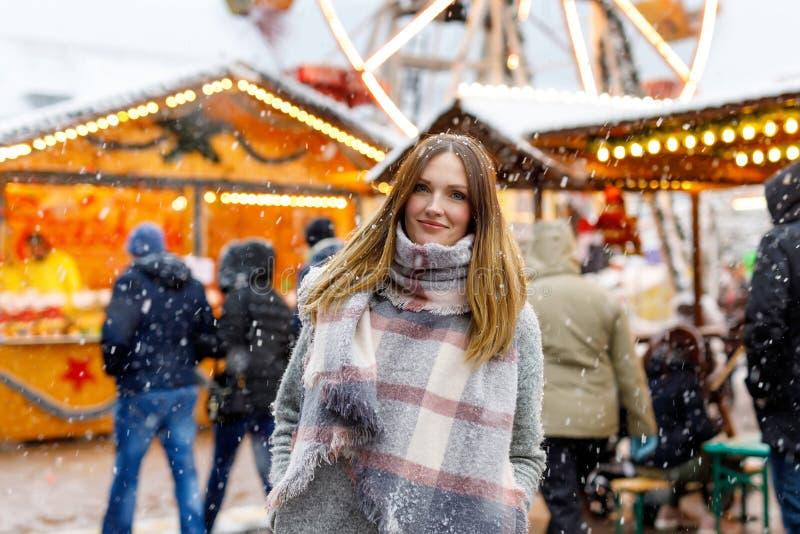 Bella giovane donna divertendosi sul mercato tedesco tradizionale di Natale durante le forti precipitazioni nevose immagine stock