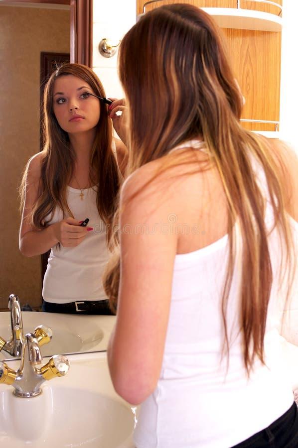 Bella giovane donna durante i makeups immagini stock