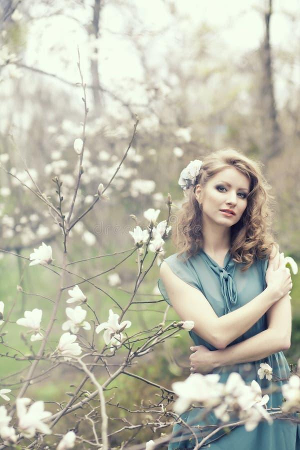 Bella giovane donna e rmagnolia di fioritura fotografie stock libere da diritti