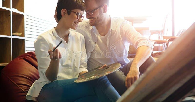 Bella giovane donna e un uomo bello che assiste insieme ad un'officina della pittura fotografia stock