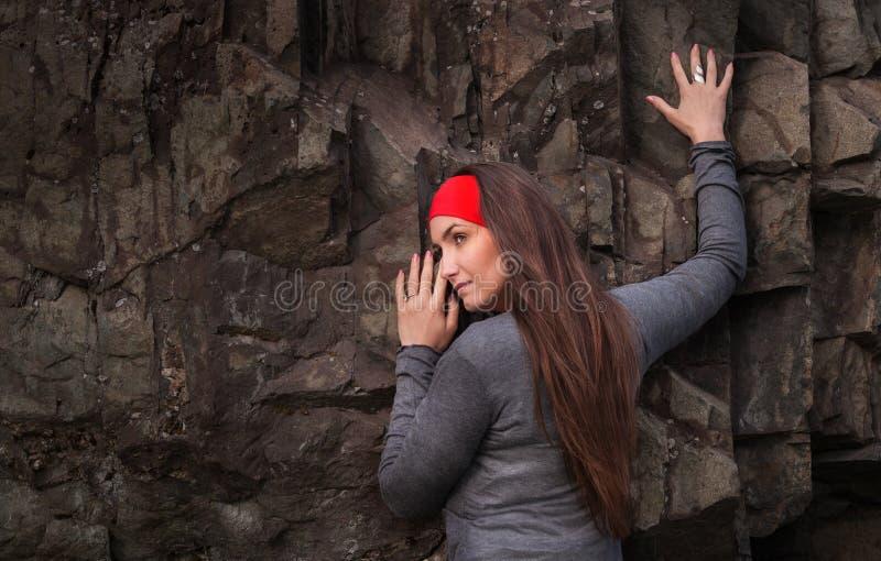 Bella giovane donna in fascia rossa alla roccia immagini stock libere da diritti