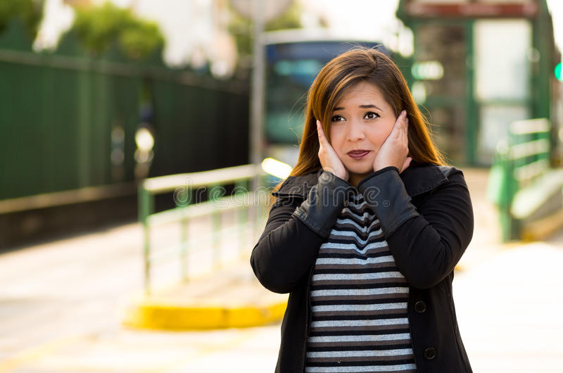 Bella giovane donna felice che copre le sue orecchie di entrambe le mani sulla via nella città con inquinamento sano con la a fotografia stock libera da diritti