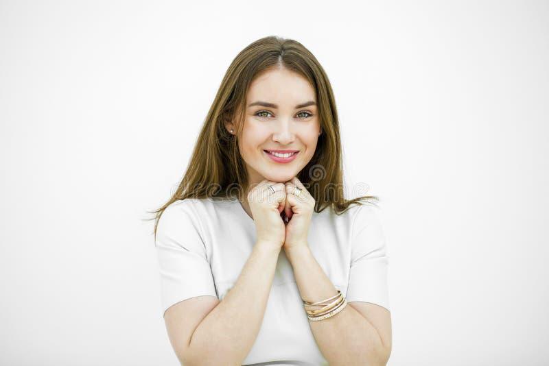 Bella giovane donna felice che posa contro una parete bianca fotografia stock libera da diritti
