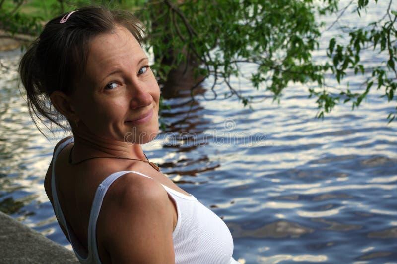 Bella giovane donna felice che sorride e che esamina macchina fotografica, acqua vicina stante sul lago fotografia stock