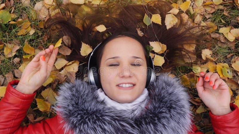 Bella giovane donna felice con le cuffie che si trovano sulle foglie di autunno che ascolta la musica Stagione, tecnologia e la g immagine stock