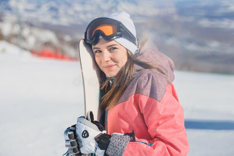 Bella giovane donna felice con lo snowboard in sue mani che esaminano macchina fotografica immagini stock
