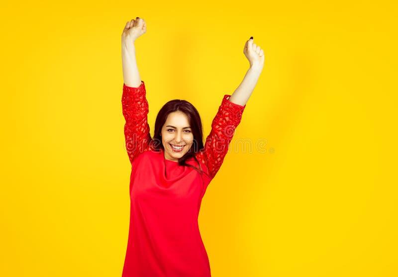 Bella giovane donna felice su un fondo giallo immagine stock libera da diritti