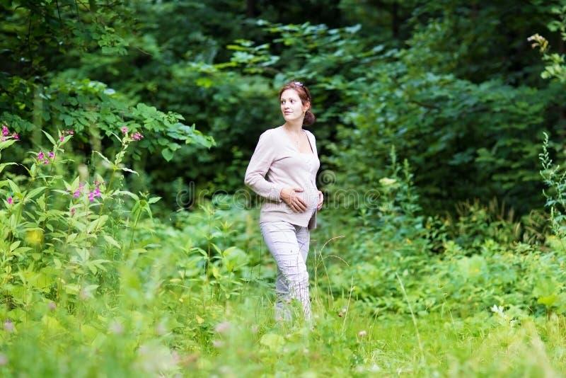 Bella giovane donna incinta che cammina in un parco fotografie stock libere da diritti