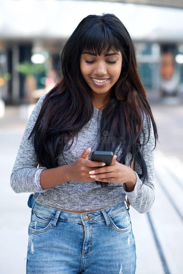 Bella giovane donna indiana che cammina con il telefono cellulare all'aperto nella città immagine stock libera da diritti