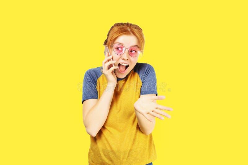 Bella giovane donna intestata rossa che posa, mostrante le espressioni facciali emozionali e facente i fronti divertenti con il t immagine stock libera da diritti