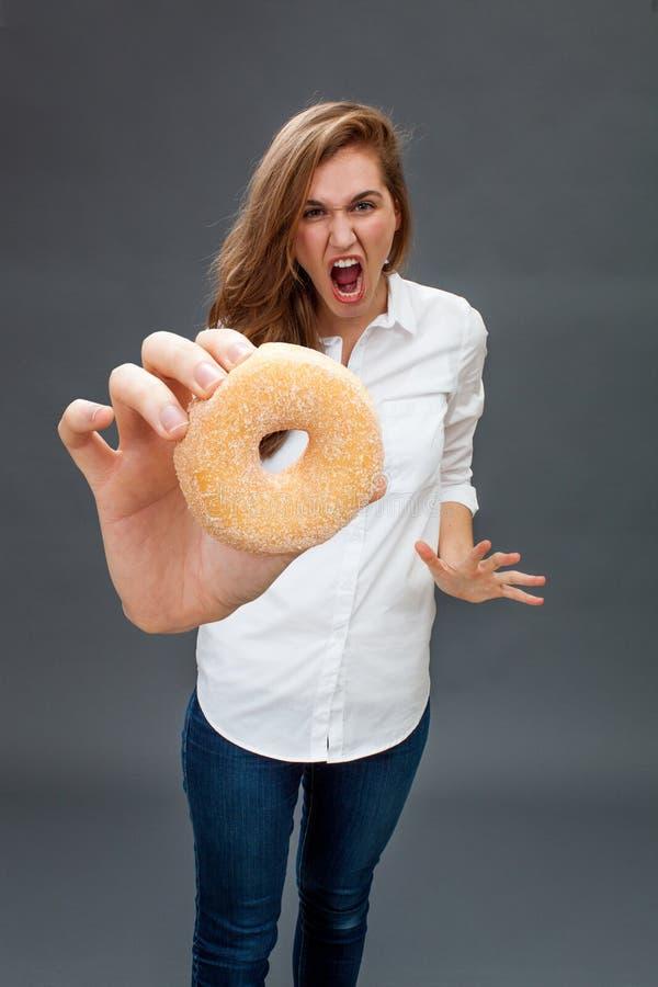 Bella giovane donna isterica che grida contro una ciambella grassa fotografie stock libere da diritti