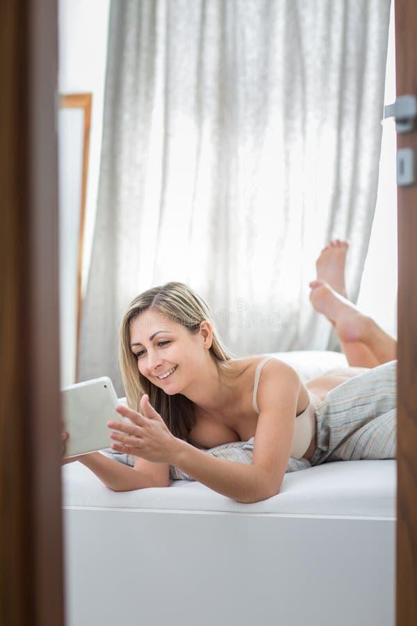 Bella giovane donna a letto, facendo uso del suo computer della compressa immagini stock libere da diritti