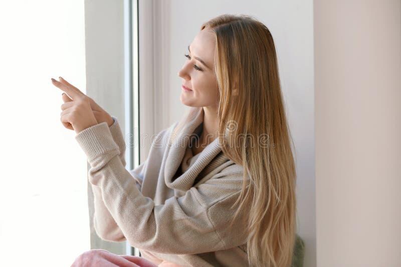 Bella giovane donna in maglione caldo che attinge il vetro di finestra a casa fotografia stock libera da diritti