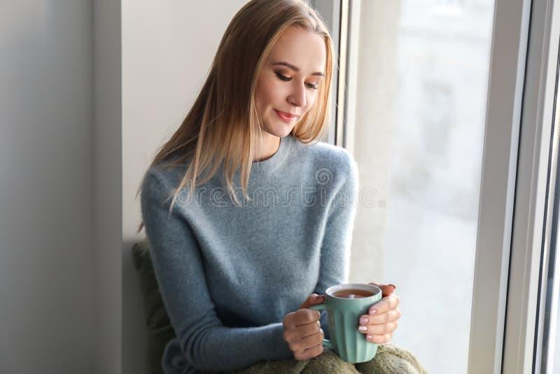 Bella giovane donna in maglione caldo che beve tè caldo sul davanzale a casa immagini stock libere da diritti