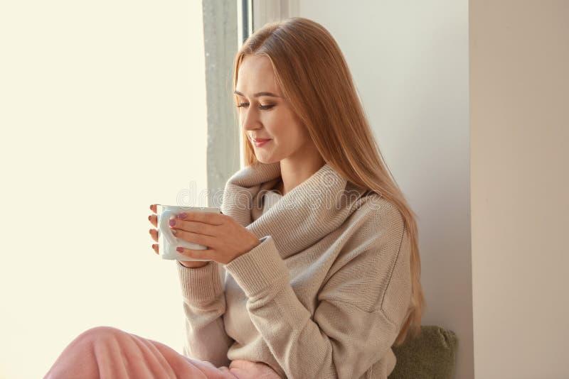 Bella giovane donna in maglione caldo che beve tè caldo sul davanzale a casa immagine stock libera da diritti