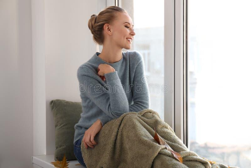 Bella giovane donna in maglione caldo che si siede sul davanzale a casa immagine stock