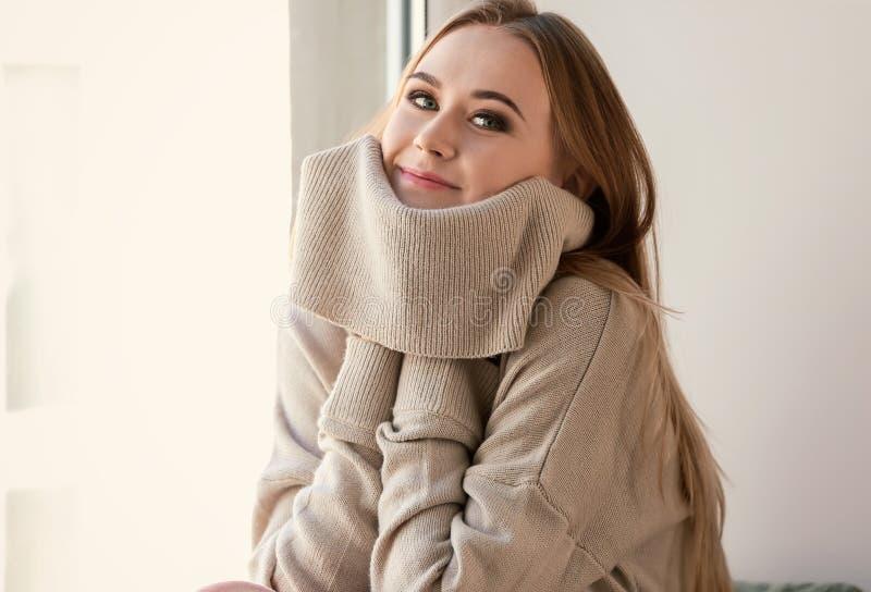 Bella giovane donna in maglione caldo che si siede vicino alla finestra a casa immagini stock