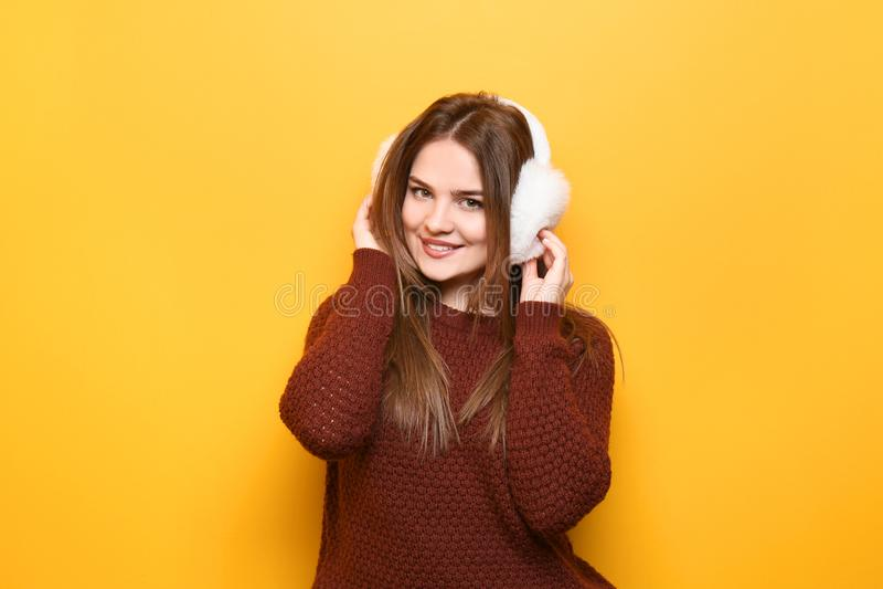 Bella giovane donna in maglione caldo e cuffia sul fondo di colore immagini stock