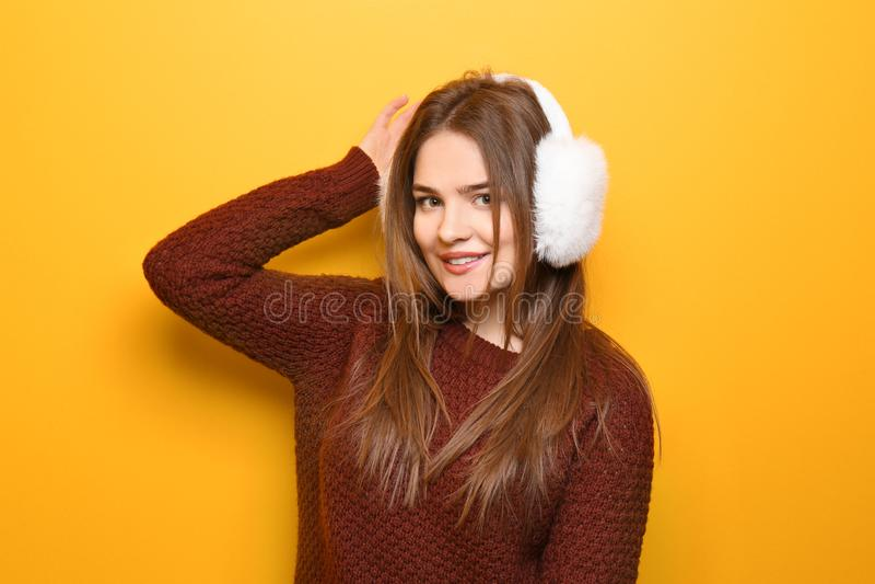 Bella giovane donna in maglione caldo e cuffia sul fondo di colore fotografia stock