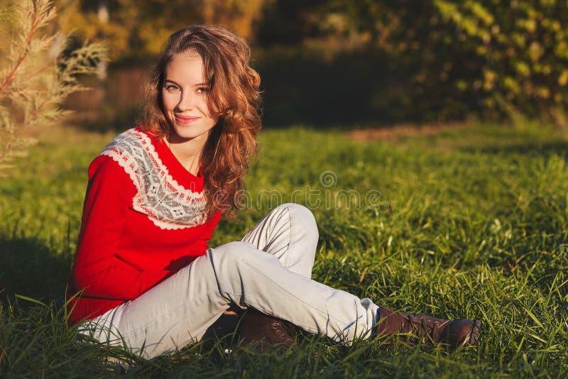 Bella giovane donna in maglione rosso nel parco di autunno immagini stock