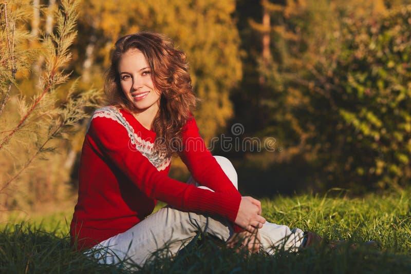 Bella giovane donna in maglione rosso nel parco di autunno fotografia stock libera da diritti