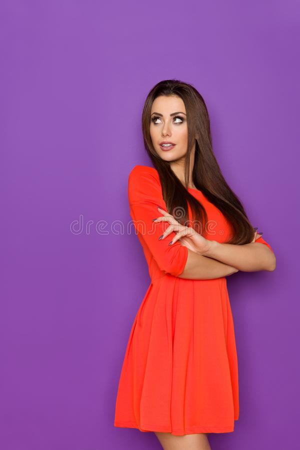 Bella giovane donna in Mini Dress Is Looking Away rosso fotografia stock
