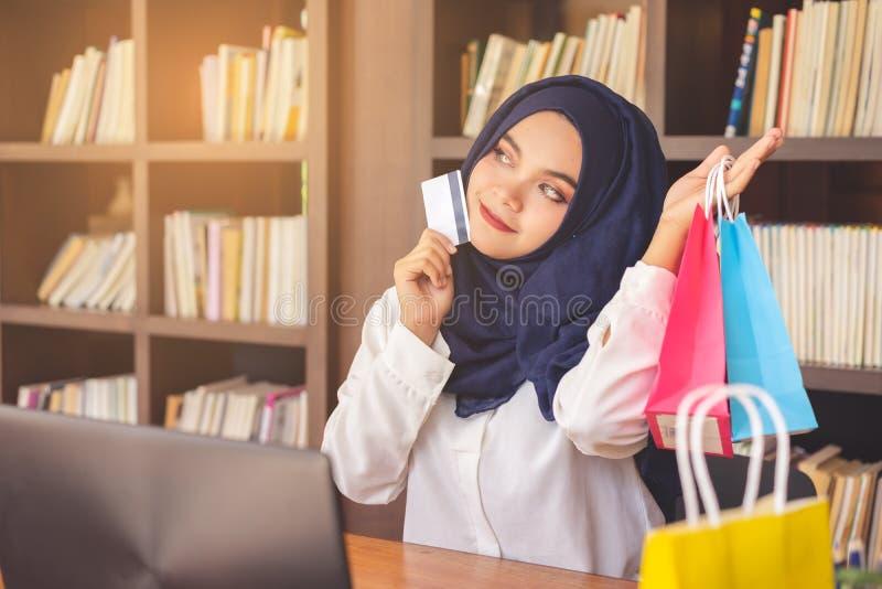 Bella giovane donna musulmana che mostra una carta di credito ed i sacchetti della spesa di carta variopinti fotografia stock libera da diritti
