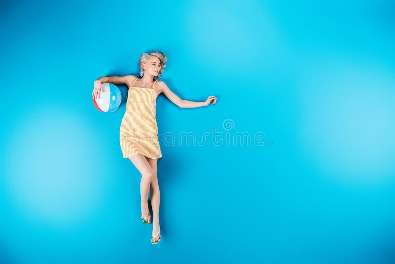bella giovane donna nei Flip-flop che tengono beach ball e distogliere lo sguardo immagine stock libera da diritti