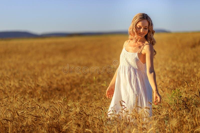 Bella giovane donna nel giacimento di grano al tramonto all'aperto fotografie stock libere da diritti