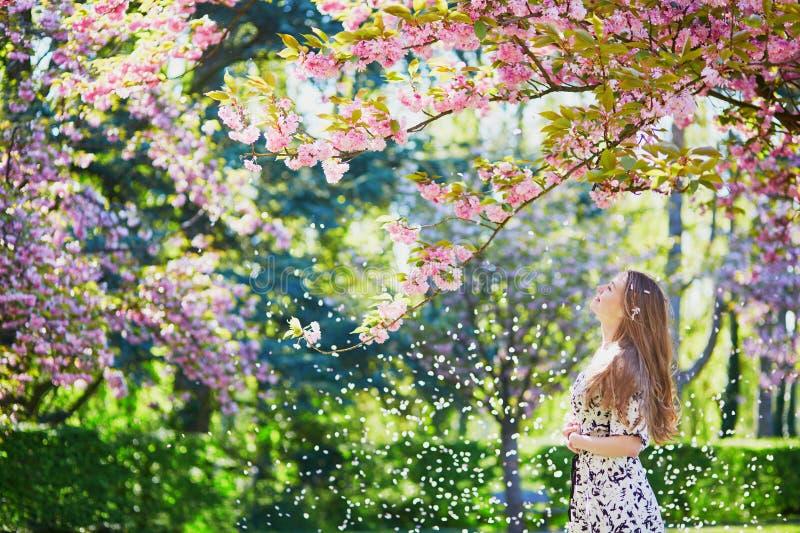 Bella giovane donna nel parco di fioritura della molla immagini stock libere da diritti